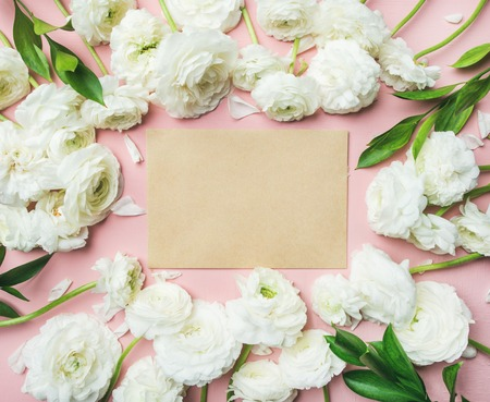 Floral layout with natural flowers. Flat-lay of tender white ranunculus over light pink background, top view, copy space. Womens day, Valentines or lovers day greeting card or weeding invitation