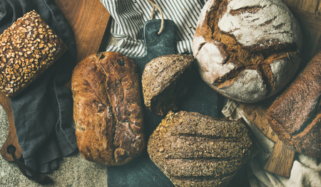 Flat-lay of various bread selection. Rye, wheat and multigrain rustic bread loaves on kitchen towels and boards over grey concrete stone background, top view, wide composition