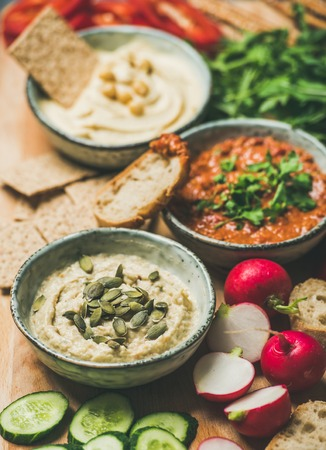 Vegan snack board. Various Vegetarian dips hummus, babaganush and muhammara with crackers, bread and fresh vegetables, wooden background. Clean eating, dieting food concept