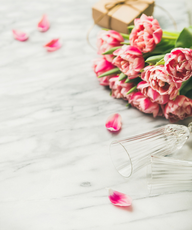 Valentines day holiday background. Bouquet of pink tulips, champaign glasses and gift box with ribbon over white marble table, copy space. Lovers or Womens day greeting card