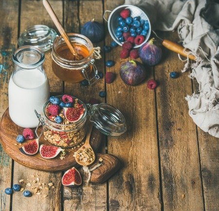 Healthy vegan breakfast. Oatmeal granola with bottled almond milk, honey, fresh fruit and berries on hoard over rustic wooden table background, copy space. Clean eating, weight loss food concept
