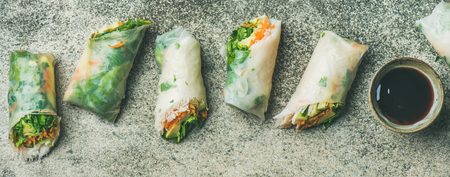 Helathy Asian cuisine. Flat-lay of vegan spring rice paper rolls with vegetables, soy sauce, chopsticks over concrete background, top view, wide composition. Clean eating, dieting, vegetarian food Stockfoto