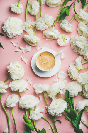 Spring morning concept. Flat-lay of cup of coffee surrounded with white ranunculus flowers over light pink background, top view Stock Photo