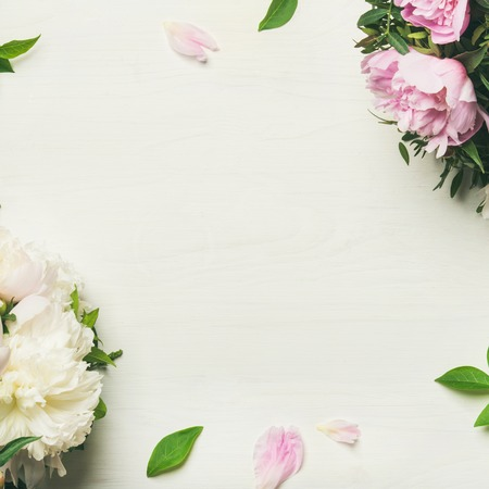 Spring flowers layout. Flat-lay of tender pale pink and white peonies over white background, top view, copy space, square crop. Womens, Valentines or lovers day greeting card or wedding invitation Stock Photo