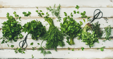 Flat-lay of bunches of various fresh green kitchen herbs. Parsley, mint, dill, cilantro, rosemary, thyme over white wooden background, top view. Spring or summer healthy vegan cooking concept Banque d'images