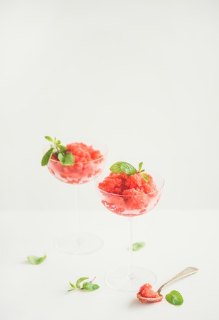 Healthy low calorie summer treat. Strawberry and champaigne granita or shaved ice dessert with fresh mint in champaigne glasses, white background, copy space. Clean eating, vegetarian food concept Stock Photo
