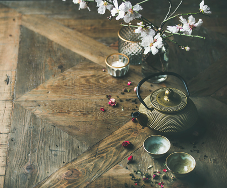 Traditional Asian tea ceremony arrangement. Golden iron teapot, cups, candles and almond blossom flowers over vintage wooden table backgrond, copy space.