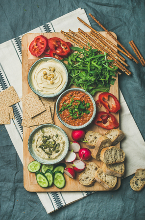 Vegan snack board. Various Vegetarian dips hummus, babaganush and muhammara with crackers, bread and fresh vegetables on wooden board over grey linen background. Clean eating, dieting food concept Stock Photo