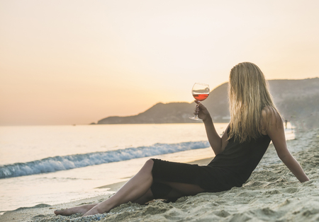 Young blond woman enjoying glass of rose wine on beach by the sea at sunset. Cleopatra beach, Alanya, Mediterranean region, Turkey.