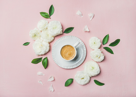 Spring morning concept. Flat-lay of cup of freshly brewed coffee surrounded with white ranunculus flowers and petals over light pink pastel background, top view Foto de archivo