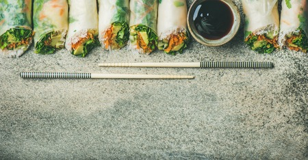 Helathy Asian cuisine. Flat-lay of vegan spring rice paper rolls with vegetables, soy sauce, chopsticks over concrete background, top view, copy space, wide composition. Clean eating, vegetarian food Stock Photo