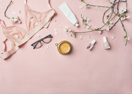 Womans morning rituals concept. Flat-lay of feminine tender powder color lingerie, glasses, cosmetic items, cup of coffee and Spring blossom flowers over pastel pink bed cover, top view, copy space.
