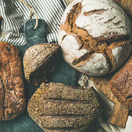 Flat-lay of various bread selection. Rye, wheat and multigrain rustic bread loaves on kitchen towels and wooden boards over grey concrete stone background, top view, square crop