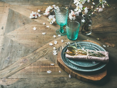 Spring Easter holiday Table setting. Tender almond blossom flowers on branches, plates, glasses and cutlery over vintage wooden table, selective focus, copy space.