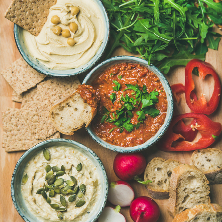 Vegan snack board. Flat-lay of various Vegetarian dips hummus, babaganush and muhammara with crackers, bread and fresh vegetables, top view, square crop. Clean eating, healthy, dieting food concept Stock Photo