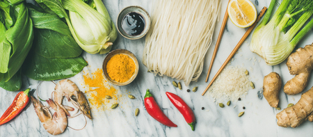 Asian cuisine ingredients over marble background, top view. Flat-lay of vegetables, spices, shrimp, sauces for cooking vietnamese, thai or chinese food. Clean eating, vegetarian concept Imagens