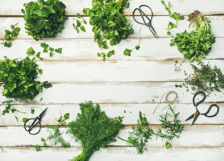 Flat-lay of bunches of various fresh green kitchen herbs. Parsley, mint, dill, cilantro, rosemary, thyme over white wooden background, top view, copy space. Healthy vegan cooking concept Imagens