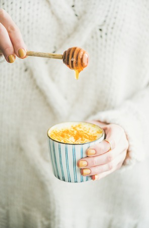 Healthy vegan turmeric latte or golden milk with honey in hands of woman wearing white sweater Фото со стока