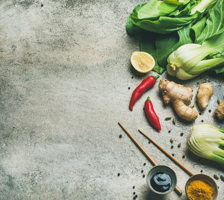 Asian cuisine ingredients over grey background, top view, copy space. Flat-lay of vegetables, spices, sauces for cooking vietnamese, thai or chinese food. Clean eating, vegetarian concept