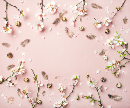 Easter holiday background. Flat-lay of tender Spring almond blossom flowers on branches, feathers, quail eggs over light pink background, top view, copy space. Greeting card concept Stock Photo