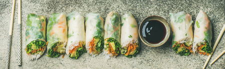 Helathy Asian cuisine. Flat-lay of vegan spring, summer rice paper rolls with vegetables, sauce, chopsticks over concrete background, top view, wide composition. Clean eating, dieting food