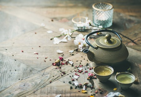 Traditional Asian tea ceremony arrangement. Iron teapot, cups, dried rose buds and candles over wooden table background, selective focus, copy space
