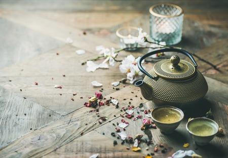 Traditionelle asiatische Teezeremonienanordnung. Bügeln Sie Teekanne, Schalen, getrocknete rosafarbene Knospen und Kerzen über Holztischhintergrund, selektiver Fokus, Kopienraum