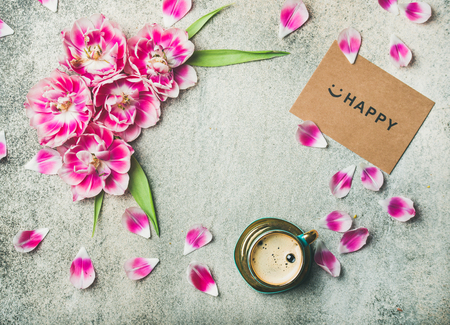 Spring morning concept. Flat-lay of cup of coffee surrounded with pink tulip flowers, petals and sign happy on paper over grey marble background, top view, copy space