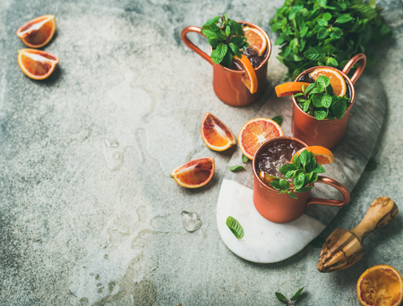 Blood orange Moscow mule alcohol cocktails with fresh mint leaves and ice in copper mugs on board over grey concrete background, copy space 스톡 콘텐츠
