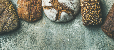 Various bread selection flat-lay. Top view of Rye, wheat and multigrain rustic bread loaves over grey background, copy space, wide composition