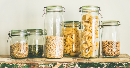 Various uncooked cereals, grains, beans and pasta for healthy cooking in glass jars on rustic table, white background, wide composition. Clean eating, vegetarian, vegan, balanced dieting food concept Stock Photo