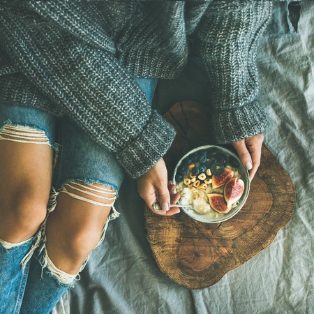 Healthy winter breakfast in bed. Woman in sweater and jeans eating rice coconut porridge with figs, berries, hazelnuts, top view, square crop. Clean eating, vegetarian, vegan, comfort food concept