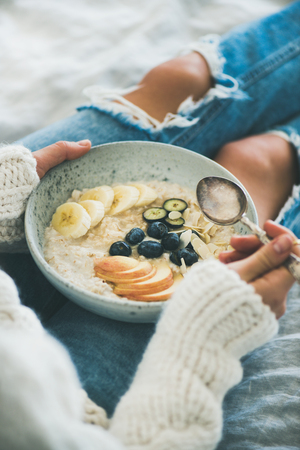 Healthy winter breakfast in bed. Woman in woolen sweater and shabby jeans eating vegan almond milk oatmeal porridge with berries, fruit and almonds, close-up. Clean eating, vegetarian food concept