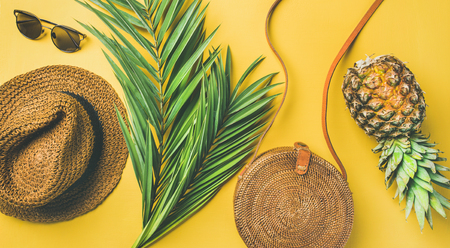 Colorful summer female fashion outfit flat-lay. Straw sunhat, bamboo bag, sunglasses, palm branches and pineapple over yellow background, top view, wide composition. Summer vacation fashion concept