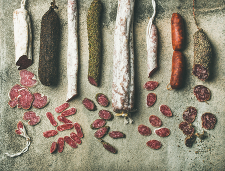 Variety of Spanish or Italian cured meat sausages. Flat-lay of fuets and salamies cut in slices over rough grey concrete background, top view