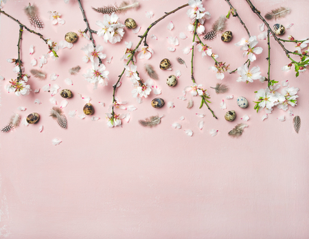 Easter holiday background. Flat-lay of tender Spring almond blossom flowers on branches, feathers and quail eggs over light pink background, top view, copy space. Greeting card concept Foto de archivo
