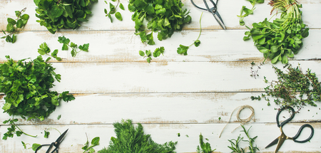 Flat-lay of bunches of various fresh green herbs. Parsley, mint, dill, cilantro, rosemary, thyme over wooden background, top view, copy space, wide composition. Healthy vegan cooking concept