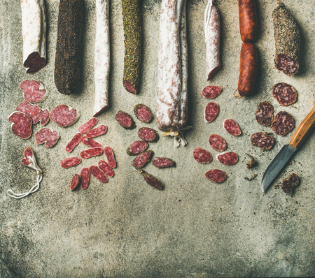 Variety of Spanish or Italian cured meat sausages. Flat-lay of fuets and salamies cut in slices over rough grey concrete background, top view, copy space 版權商用圖片