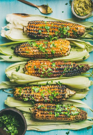 Summer vegan dinner or snack. Flat-lay of grilled sweet corn with smoked sea salt, cilantro and homemade pesto sauce over blue background, top view. Vegetarian, healthy, alkaline diet concept Reklamní fotografie