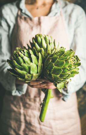 Female farmer wearing pastel linen apron and shirt holding fresh artichokes in her hands, selective focus. Organic produce or local market concept