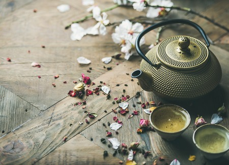 Traditional Asian tea ceremony arrangement. Iron vintahe teapot, cups, blooming almond flowers, dried rose buds and candles over wooden table background, selective focus, copy space Stock Photo