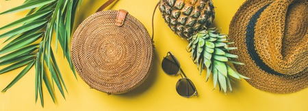 Colorful summer female fashion outfit flat-lay. Straw hat, bamboo bag, sunglasses, palm branches, pineapple over yellow background, top view, wide composition. Summer fashion, holiday concept Stockfoto