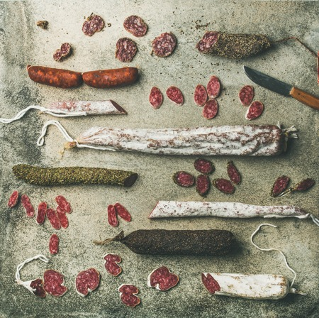 Variety of Spanish or Italian cured meat sausages. Flat-lay of fuets and salamies cut in slices and knife over rough grey concrete background, top view