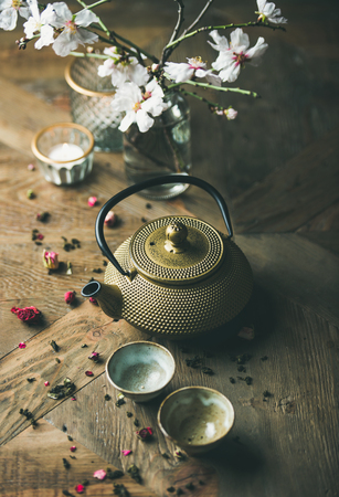 Traditional Asian tea ceremony arrangement. Golden iron teapot, cups, dried rose, candles and almond blossom flowers over vintage wooden table background, selective focus Stock Photo - 100151028