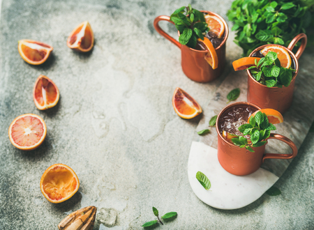 Blood orange Moscow mule alcohol cocktails with fresh mint leaves and friuts and ice in copper mugs on board over grey concrete background, copy space Stockfoto