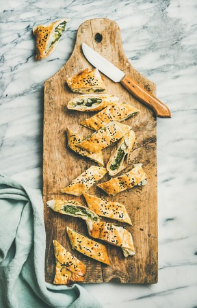 Flat-lay of fresh Turkish borek roll cut in slices slices with spinach, feta cheese, black cumin seeds on wooden board over grey marble background, top view. Traditional East Mediterranean cuisine