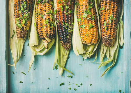 Summer vegan dinner, snack. Flat-lay of grilled sweet corn with smoked sea salt and cilantro over blue background, top view, copy space. Vegetarian, healthy, clean eating, alkaline, diet concept Stok Fotoğraf