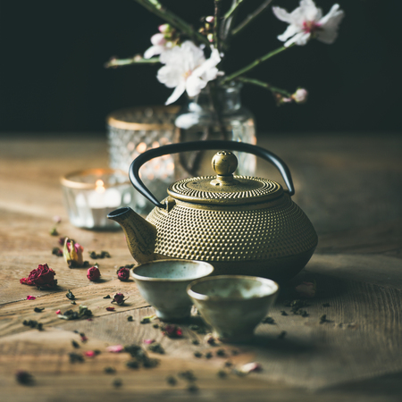 Traditional Asian tea ceremony arrangement. Golden iron teapot, cups, candles and almond blossom flowers over vintage wooden table background, selective focus, square crop