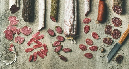 Variety of Spanish or Italian cured meat sausages. Flat-lay of fuets and salamies cut in slices over rough grey concrete background, top view, copy space, wide composition