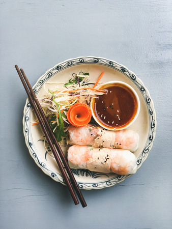 Asian style dinner. Flat-lay of summer rice paper rolls with shrimp and teriyaki sauce in bowl over blue table, top view, copy space. Chinese cuisine Imagens